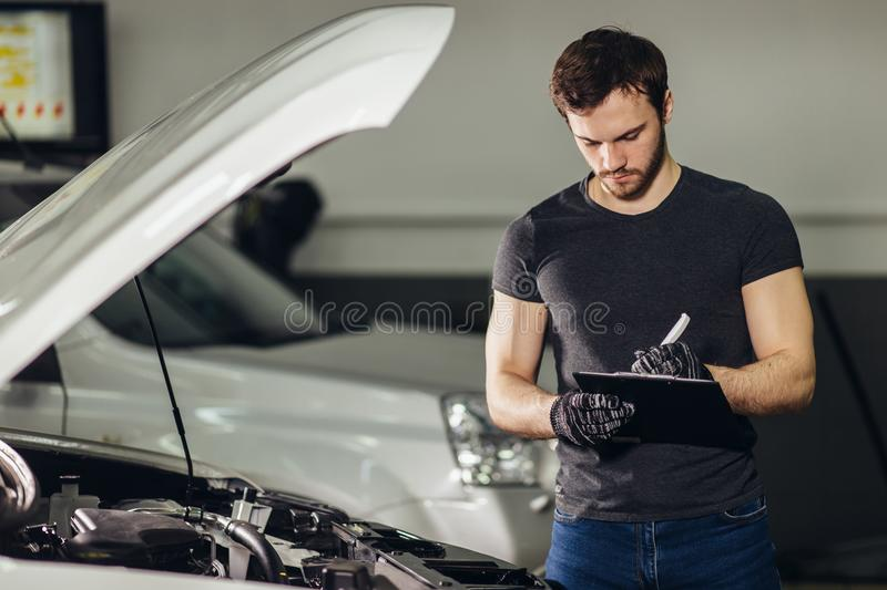 Mechachic checking on car engine and taking notes in clipboard stock images