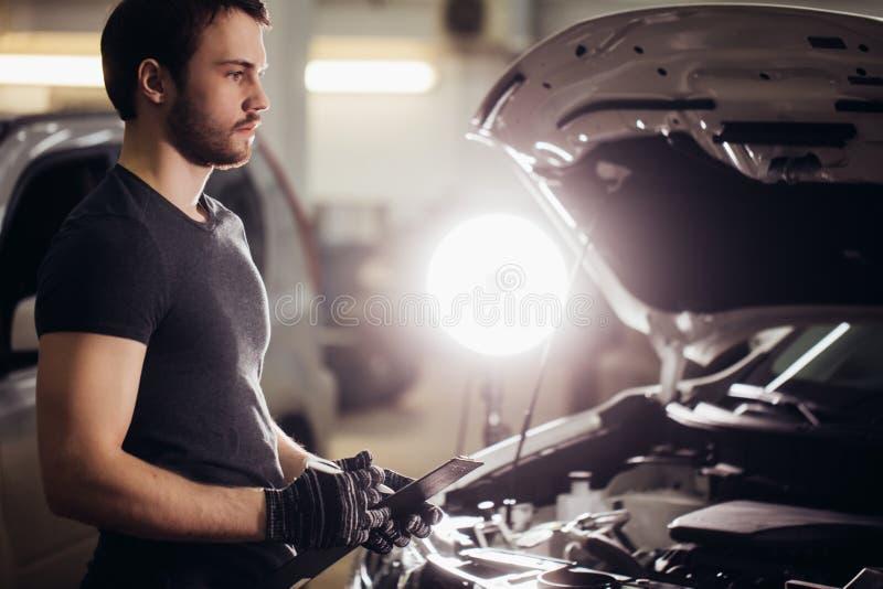 Mechachic die op motor van een auto controleren en nota's in klembord nemen royalty-vrije stock afbeelding