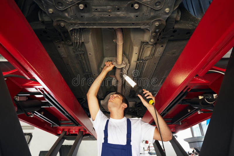 Mechanic. Standing under car engine and holding lamp. Copy space