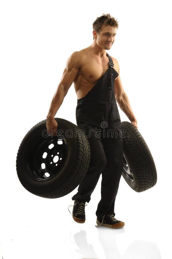 Mechanic. An attractive strong man in overalls with tire stock photo