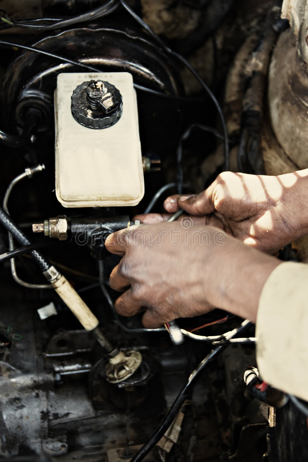 Mechanic. African American man fixing the brakes in an old car, seventies lomo look royalty free stock photos