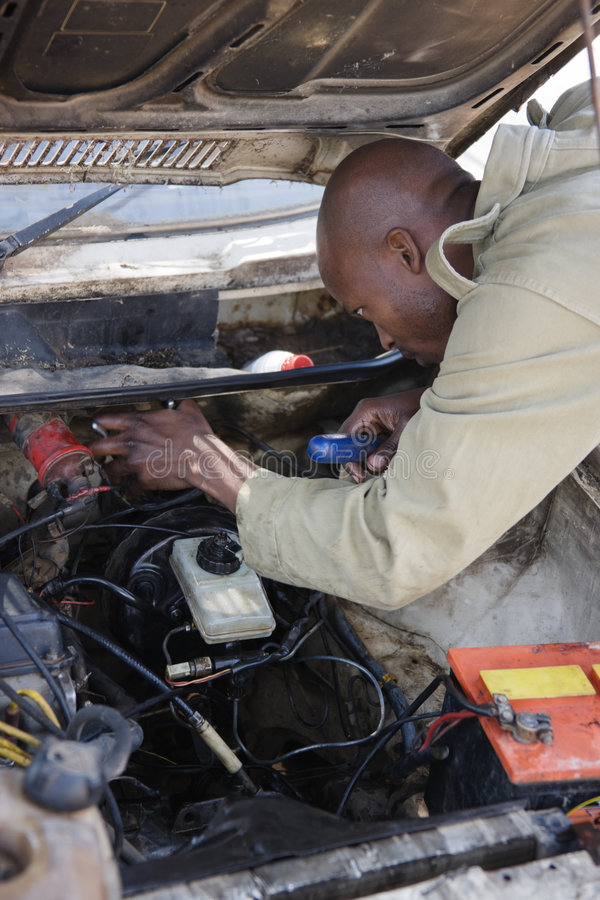 Mechanic. African American man fixing the brakes in an old car royalty free stock photo