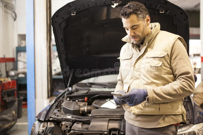 The mechanic works in the workshop royalty free stock photo