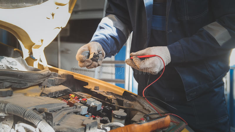 Mechanic in auto workshop works with car electrics - electrical wiring, voltmeter stock photography