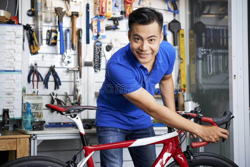 Mechanic with bicycle in workshop royalty free stock photo