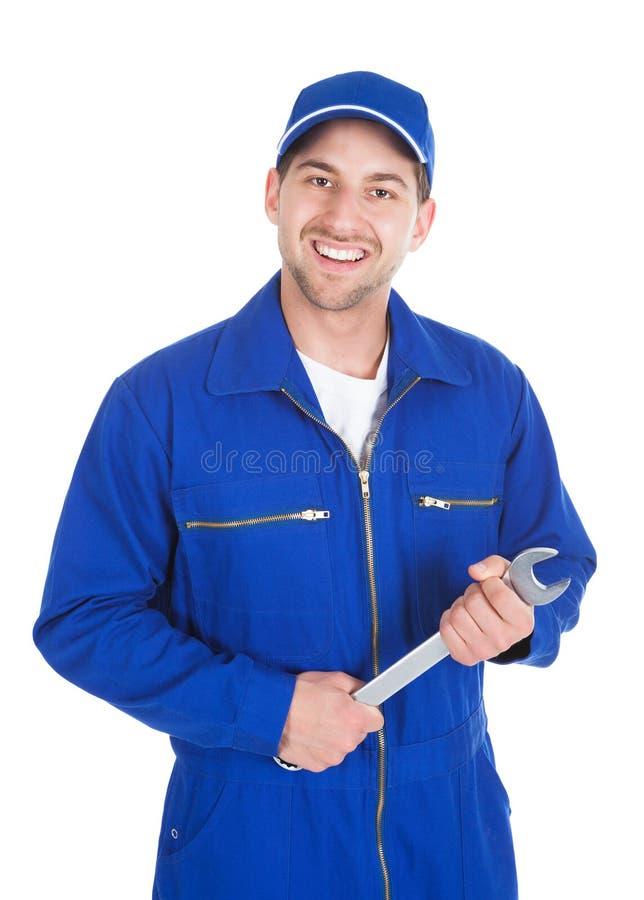 Mechanic in blue overalls holding spanner. Portrait of young male mechanic in blue overalls holding spanner over white stock photos