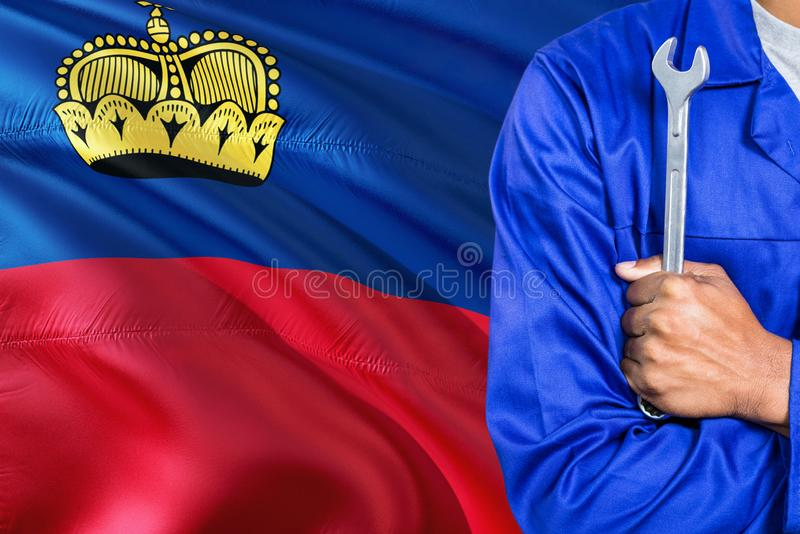 Mechanic in blue uniform is holding wrench against waving Liechtenstein flag background. Crossed arms technician royalty free stock photo