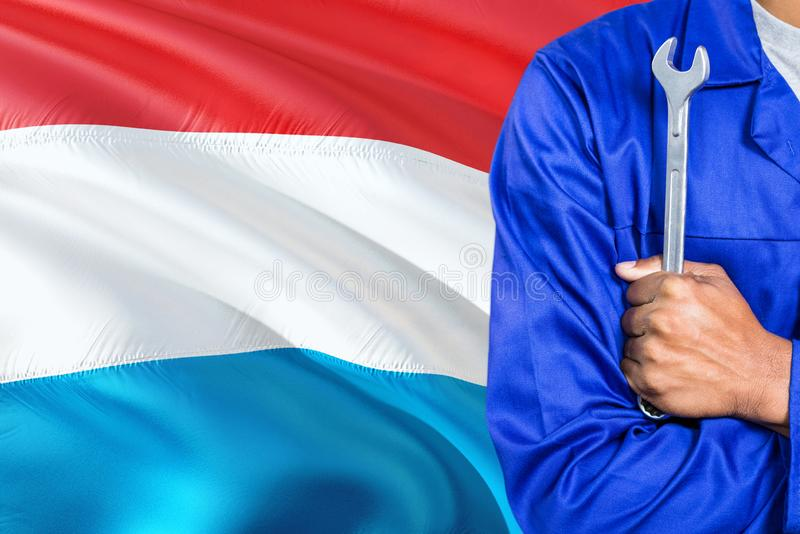Mechanic in blue uniform is holding wrench against waving Luxembourg flag background. Crossed arms technician royalty free stock photos