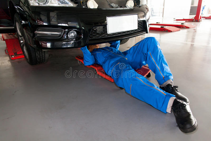 mechanic in blue uniform lying down and working under car at the stock photo image of. Black Bedroom Furniture Sets. Home Design Ideas