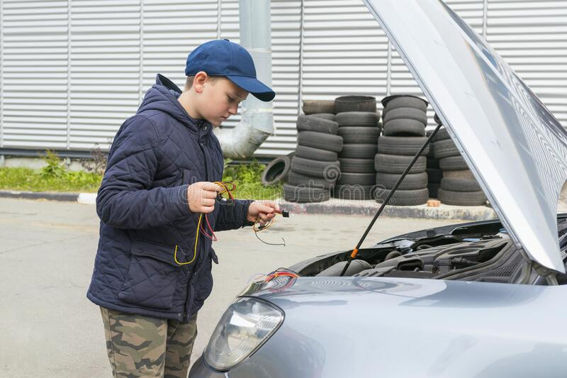 Mechanic boy working and repairing a car in a garage.  Repair service.  Car service stock photography