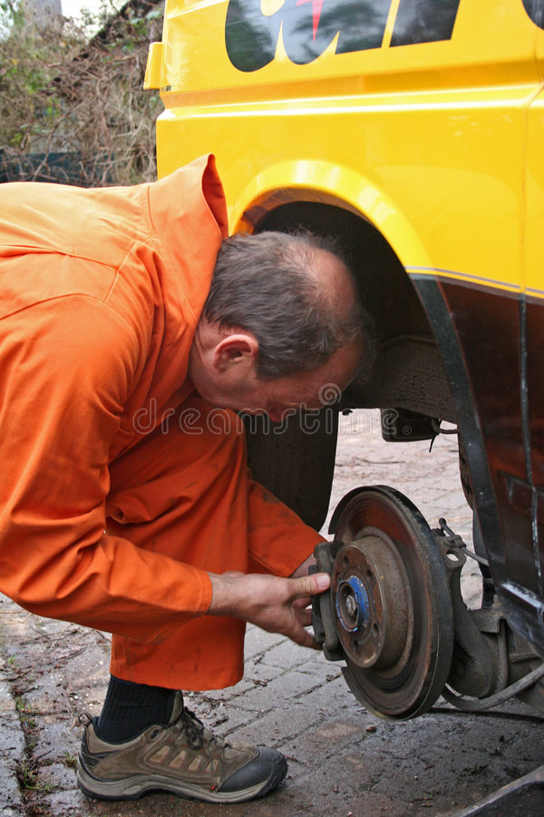 Mechanic changing brake disc stock photography