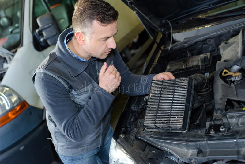 Mechanic changing car air filter. Engine stock images
