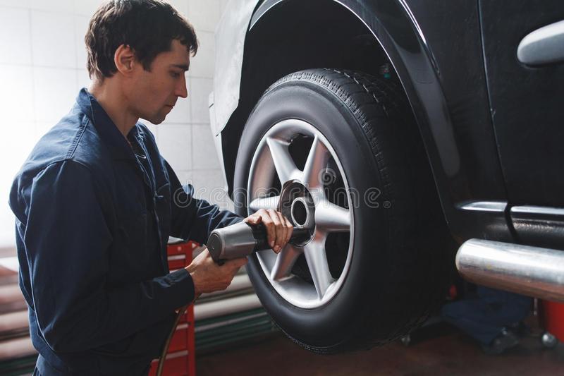 Mechanic changing car wheel in auto repair shop royalty free stock images