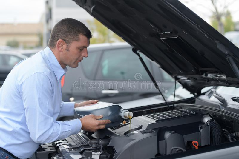 Mechanic changing motor oil to engine stock photo
