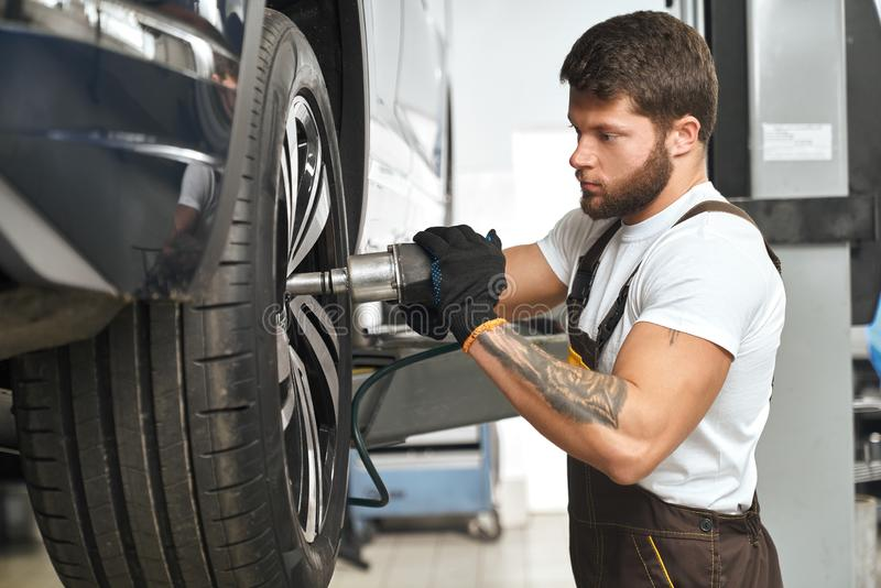 Mechanic changing wheel hubcap in automobile. Serious, concentrated mechanic changing, repairing wheel hubcap, using special equipment. Bearded, muscular man in stock images