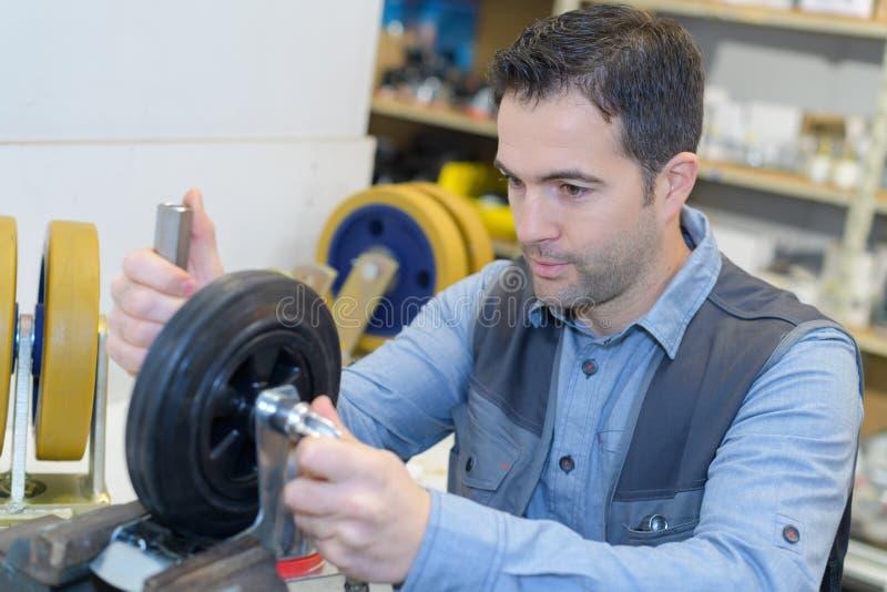 Mechanic checking car wheel rim royalty free stock photo