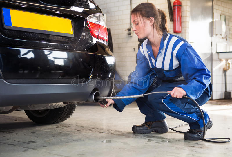 Mechanic, checking diesel exhaust emission rates. Female mechanic probing a sensor into the exhaust of a car, measuring the carbondioxide levels and emission stock image