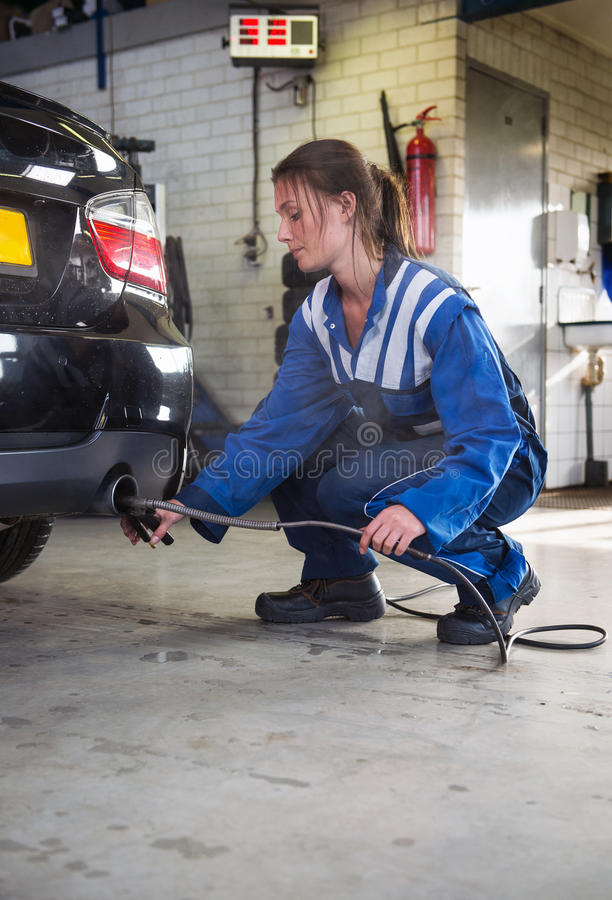 Mechanic checking diesel exhaust emission rates. Young, female mechanic, checking the disel exhaust emission rates during a periodic check, using diagnostics stock photos