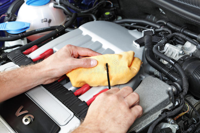 Mechanic checking motor oil. Mechanic holding a dip stick checking the engine oil on a v6 sports car stock image