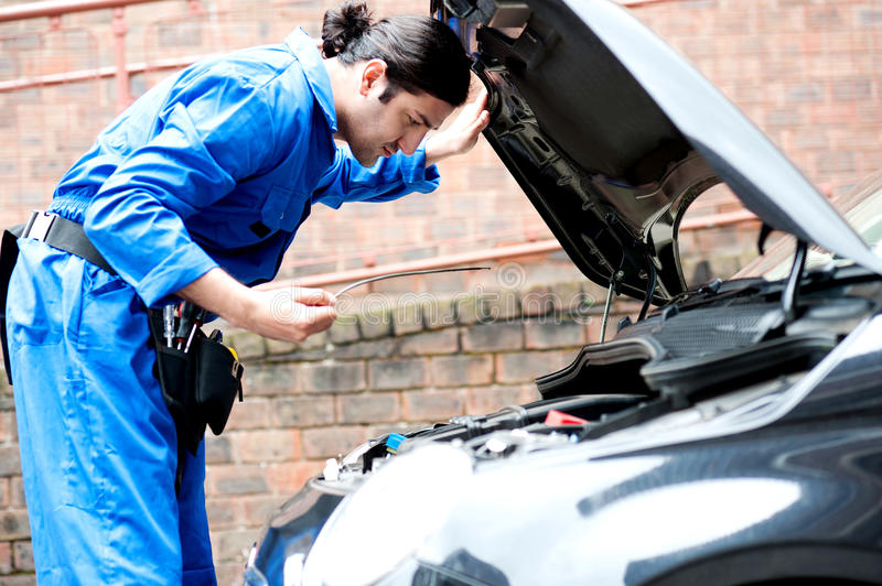 Mechanic checking the motor oil of the car royalty free stock image