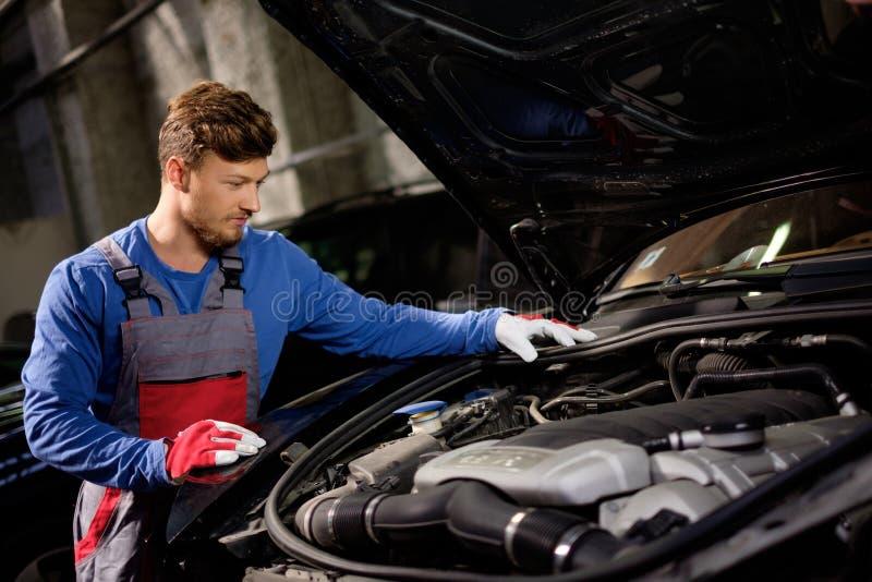 Mechanic checking under hood stock photos