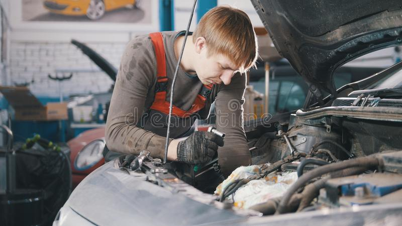 Mechanic checks and repairs automotive engine, car repair, working in the workshop, overhaul, under the hood. Wide view stock image