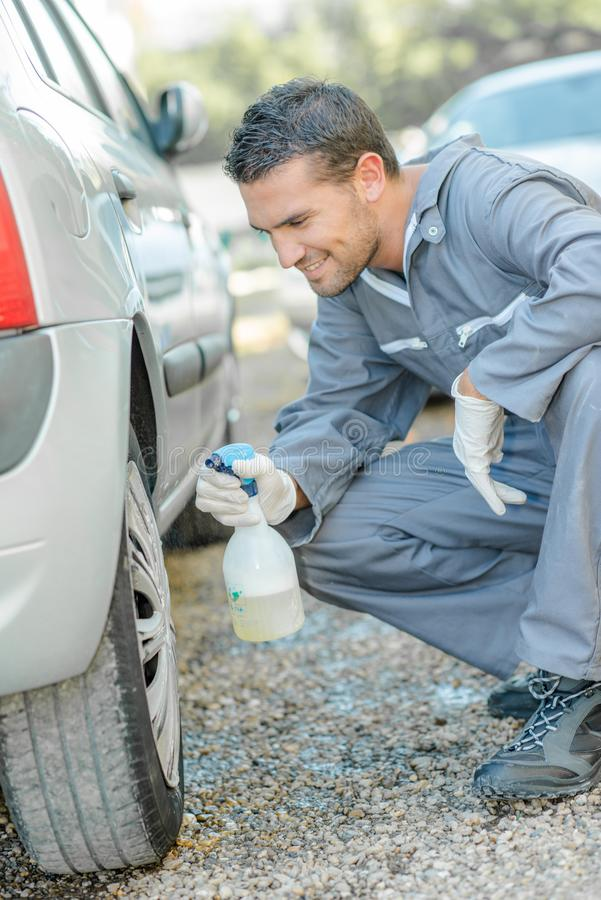 Mechanic cleaning a hubcap. Mechanic stock images