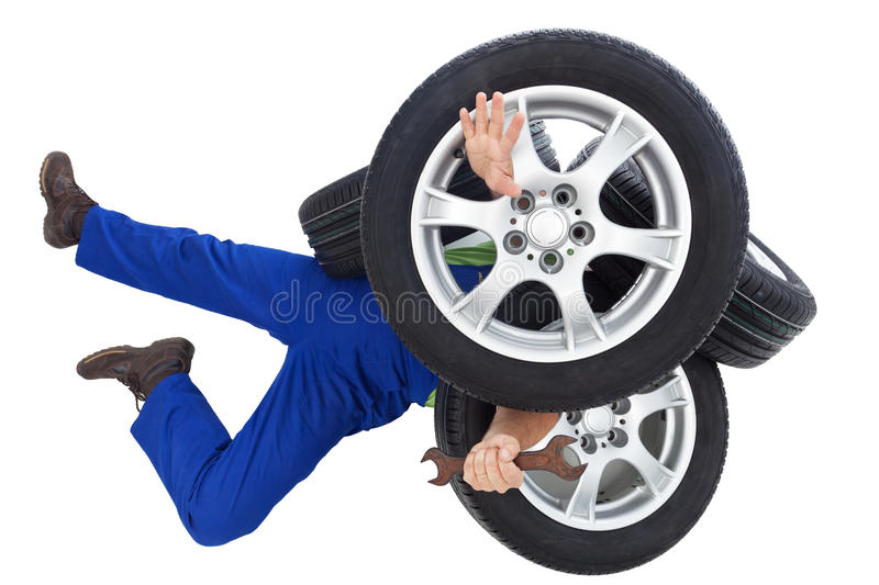 Mechanic covered by car tires stock photography