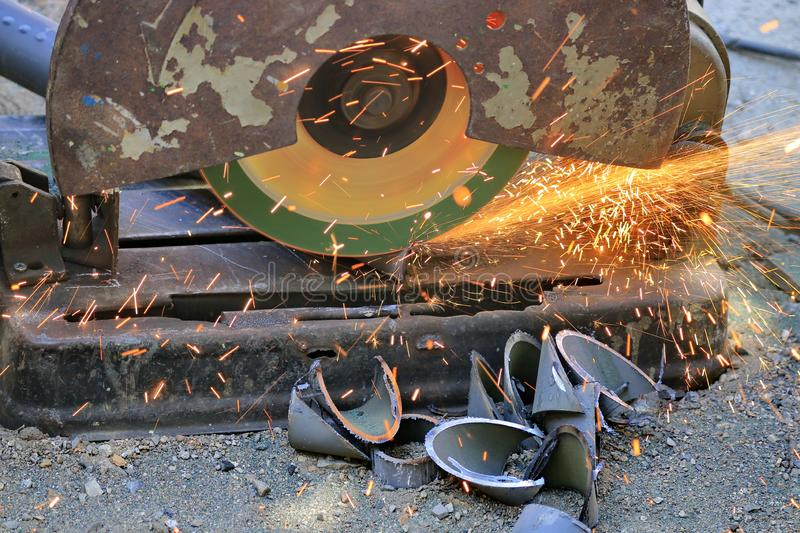 The mechanic is cutting steel with a machine with a lot of sparks.. stock photography