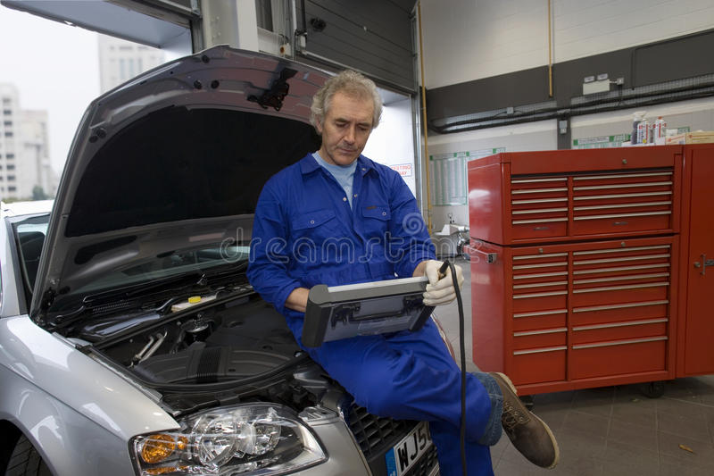 Mechanic with diagnostic computer on car with open bonnet royalty free stock photography