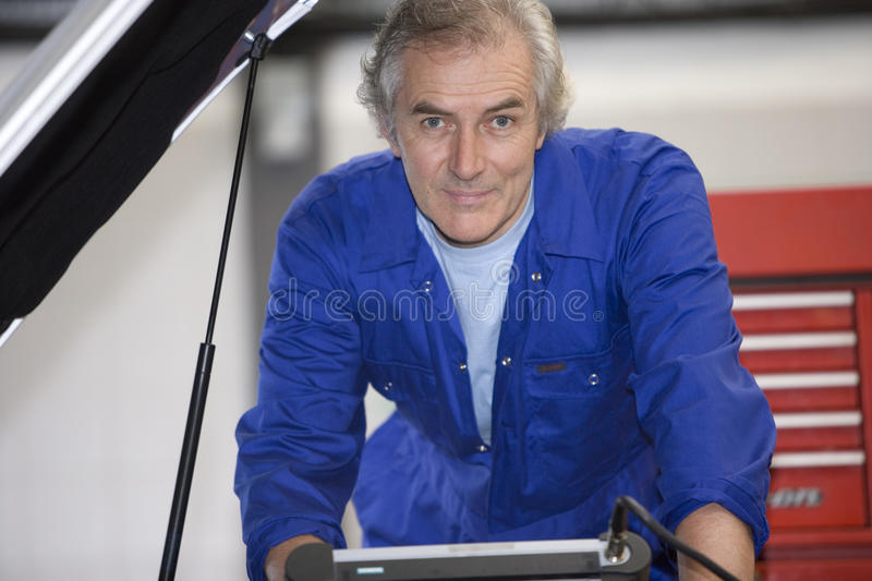 Mechanic with diagnostic computer by car with open bonnet, portrait royalty free stock photography