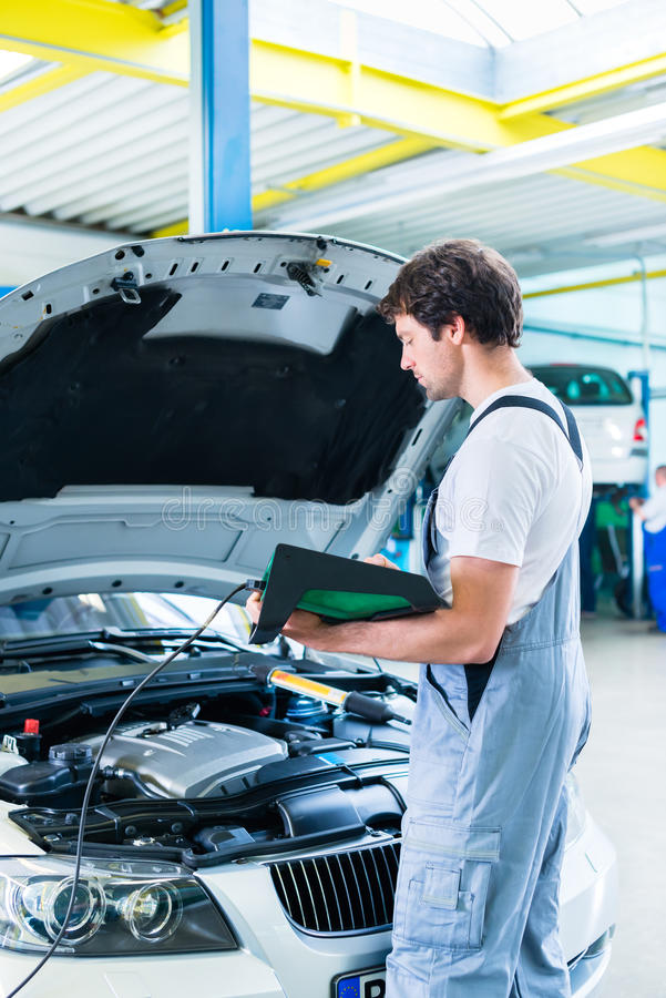 Mechanic with diagnostic tool in car workshop. Mechanic analysing engine with diagnostic tool in car workshop royalty free stock images