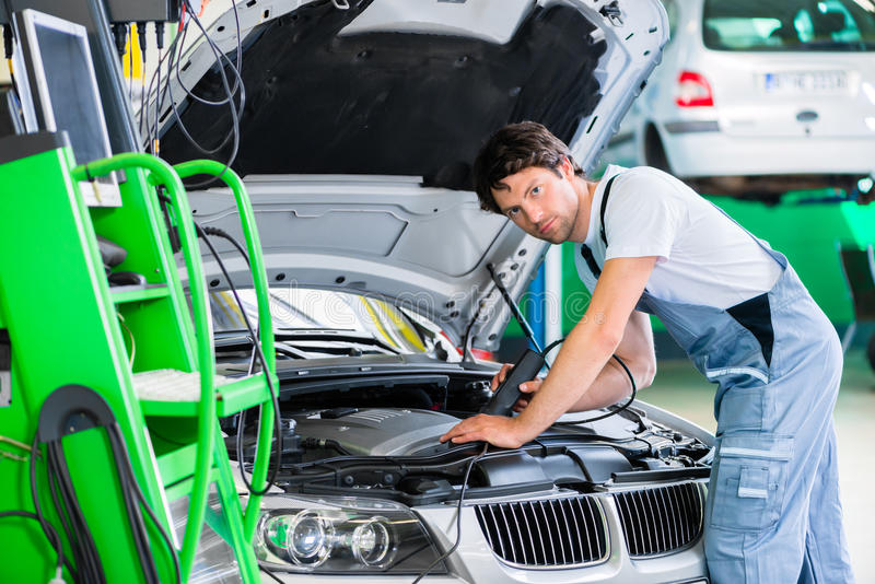 Mechanic with diagnostic tool in car workshop. Mechanic with diagnostic tool in car service workshop stock photography