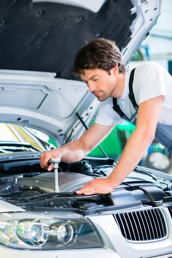 Mechanic with diagnostic tool in car workshop. Mechanic with diagnostic tool in car service workshop royalty free stock photo