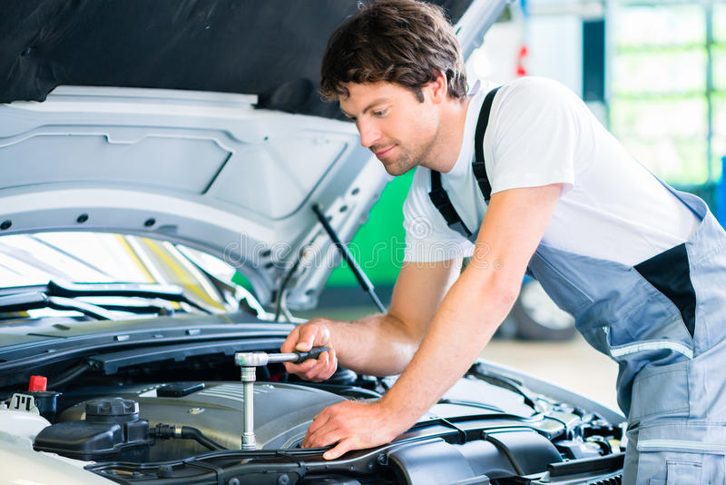 Mechanic with diagnostic tool in car workshop. Mechanic with diagnostic tool in car service workshop stock image