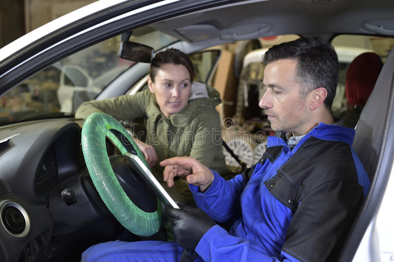 Mechanic doing car revision. Mechanic doing technical inspection on individual car royalty free stock photo