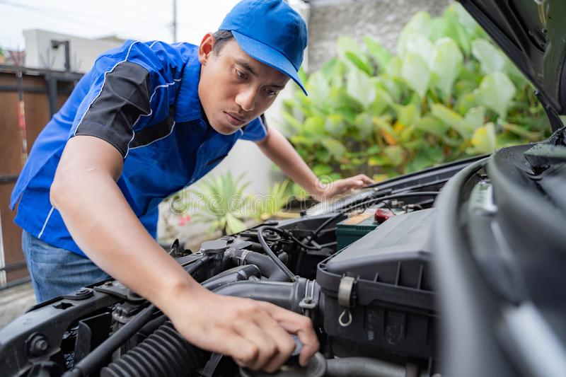 Mechanic doing some inspection on car`s engine. Home service mechanic doing some inspection on car`s engine royalty free stock image