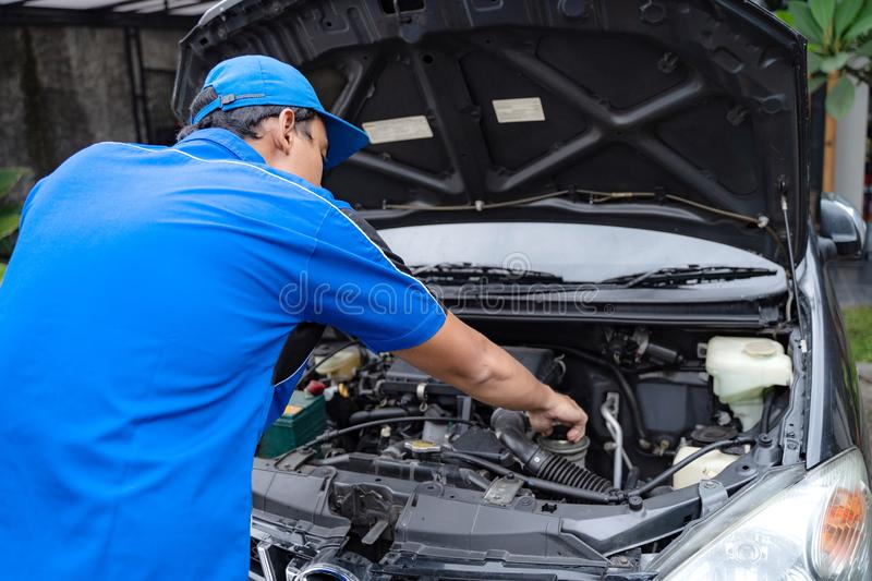 Mechanic doing some inspection on car`s engine. Home service mechanic doing some inspection on car`s engine stock images