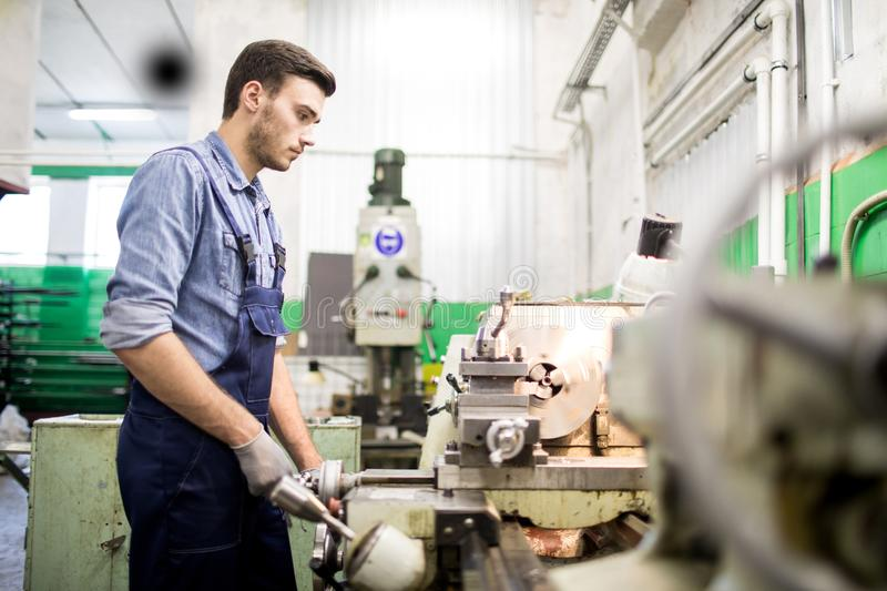 Mechanic engineer at work. Mechanical engineer in overall standing at lathe machine and controlling process of manufacture in workshop of production royalty free stock photography