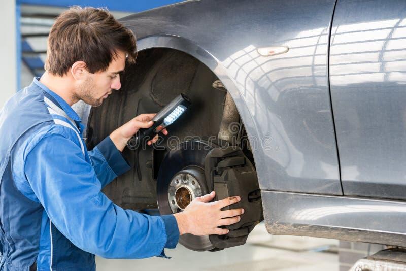 Mechanic Examining Brake Disc Of Car In Garage. Male mechanic holding flashlight while examining brake disc of car in garage stock photos