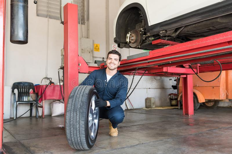 Mechanic Examining Car Tire While Crouching In Workshop. Smiling mechanic examining car tire while crouching in workshop stock photography