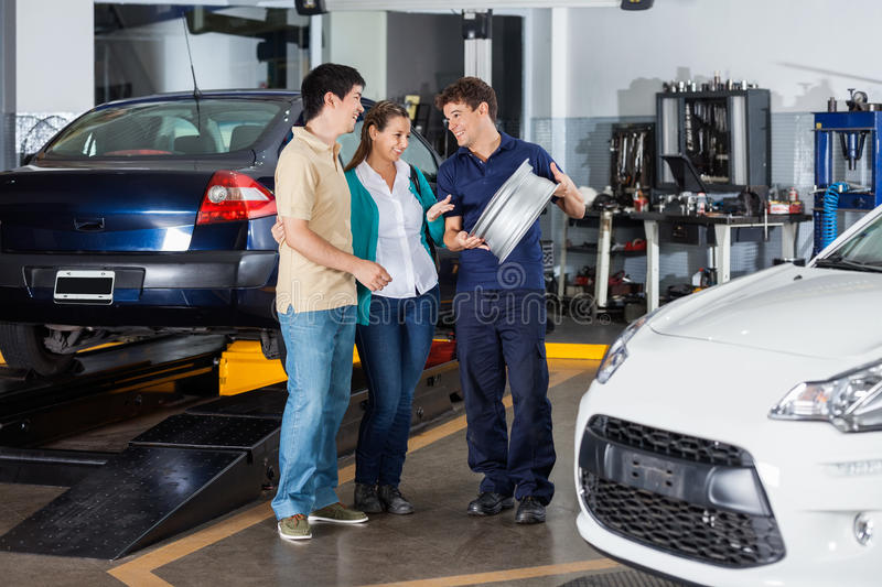 Mechanic Explaining Hubcap To Couple. Happy male technician and couple discussing over metallic hubcap at garage stock photo