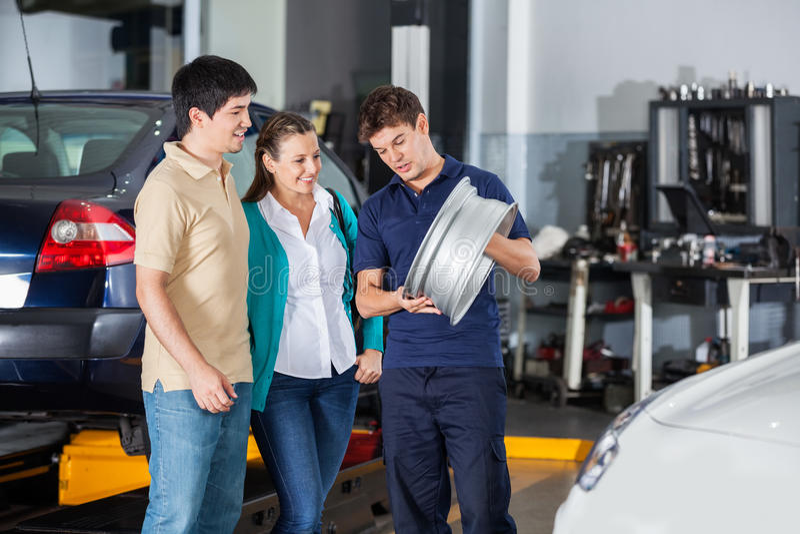 Mechanic Explaining Hubcap To Couple. Male technician explaining metallic hubcap to couple at garage stock images