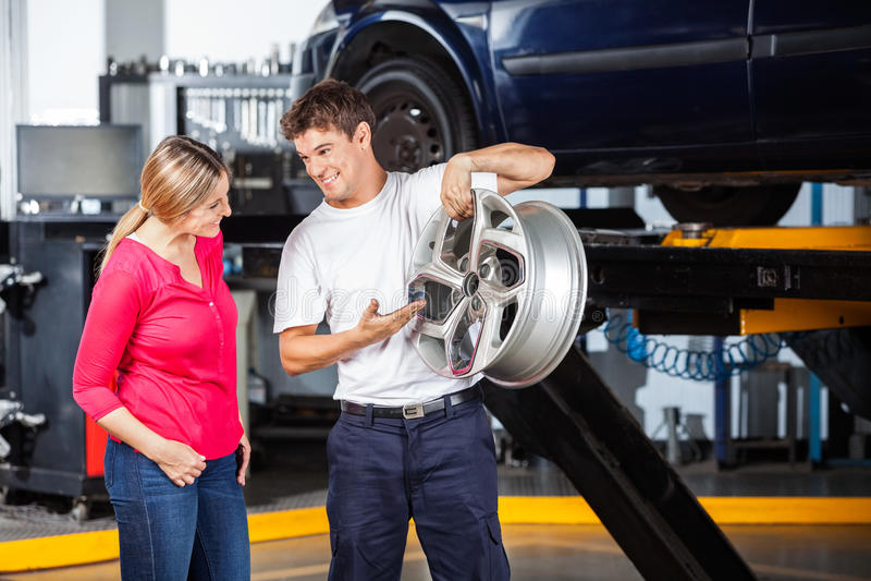 Mechanic Explaining Hubcap To Customer. Happy technician explaining metallic hubcap to female customer at garage royalty free stock photo