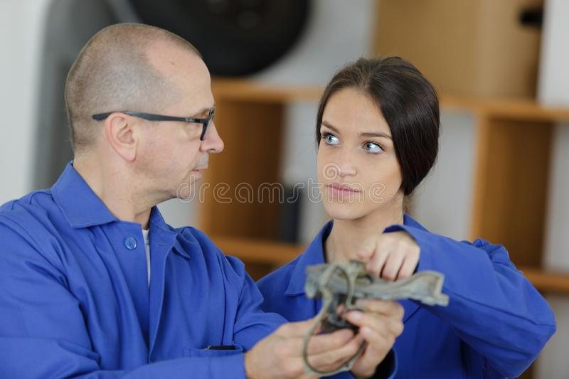 Mechanic and female trainee working together royalty free stock images