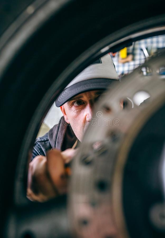 Mechanic fixing custom motorcycle wheel. In his workshop. Selective focus on mechanic in background royalty free stock photos
