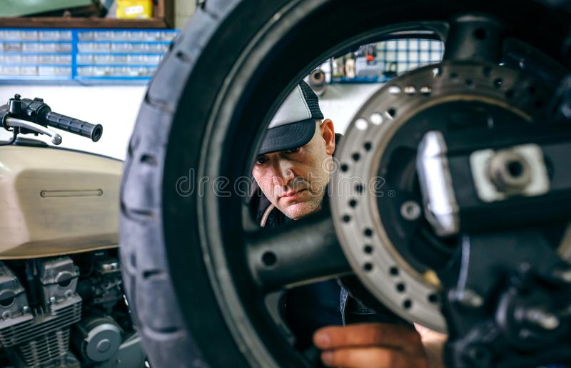 Mechanic fixing custom motorcycle wheel. In his workshop. Selective focus on mechanic in background royalty free stock photo