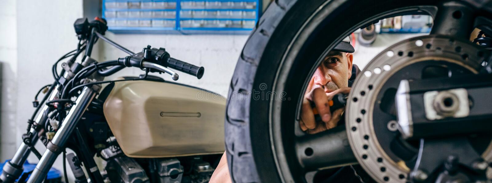 Mechanic fixing custom motorcycle wheel. In his workshop. Selective focus on mechanic in background royalty free stock images