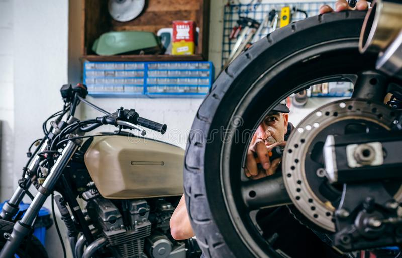 Mechanic fixing custom motorcycle wheel. In his workshop. Selective focus on mechanic in background royalty free stock image