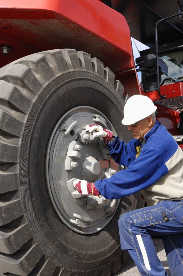 Mechanic fixing giant truck tire stock photo